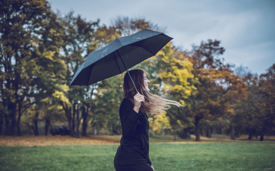 Happy young woman with umbrella walking in autumnal park